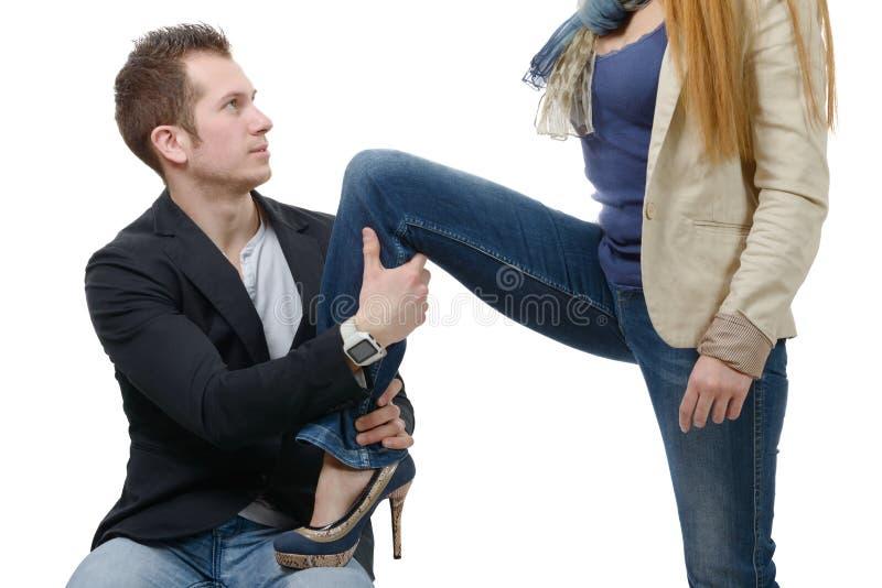 A jovem mulher ajusta o pé em seu amante imagem de stock