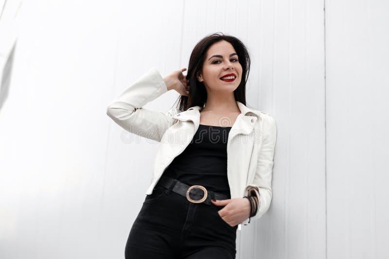 Jovem mulher alegre bonita com bordos vermelhos em um casaco de cabedal à moda em um t-shirt nas calças de brim pretas na moda qu fotografia de stock