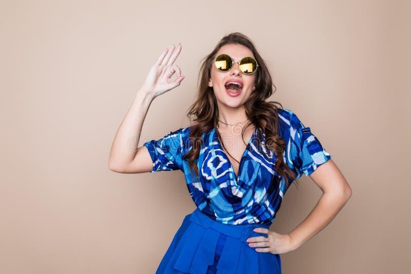 Jovem mulher alegre bonita do verão nos óculos de sol que estão sobre um fundo da cor fotografia de stock