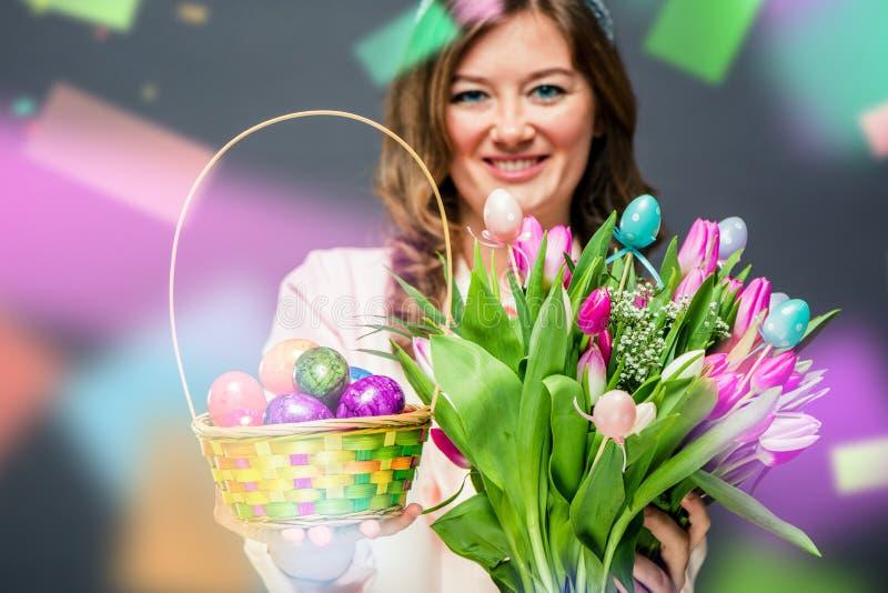 Jovem mulher alegre com as flores das orelhas do coelho e da cesta e das tulipas do ovo da páscoa que olham a câmera foto de stock
