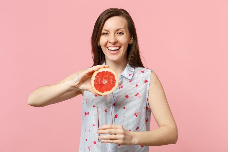 Jovem mulher alegre de sorriso na roupa do verão que guarda parcialmente do copo de vidro da toranja madura fresca isolado na cor fotografia de stock
