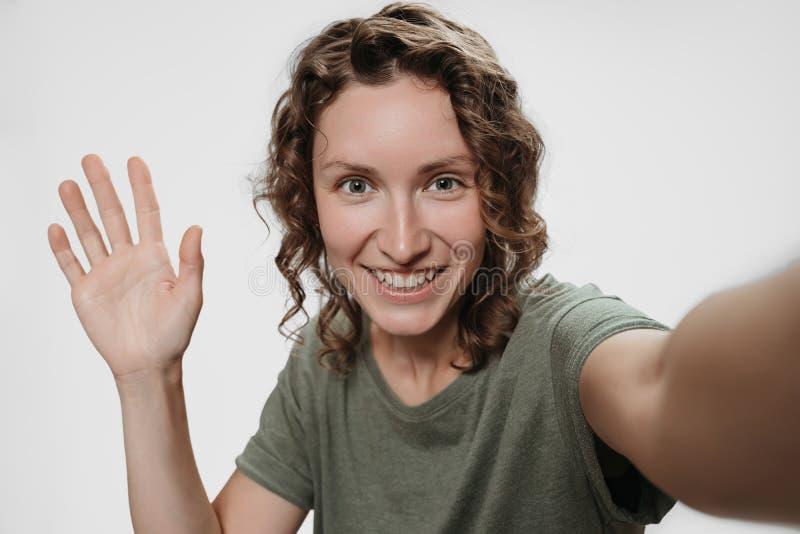 Jovem mulher alegre do retrato que tem a v?deo-chamada com os amigos que disparam no selfie fotografia de stock