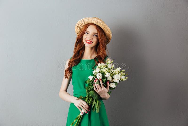 Jovem mulher alegre do ruivo que guarda flores imagens de stock royalty free
