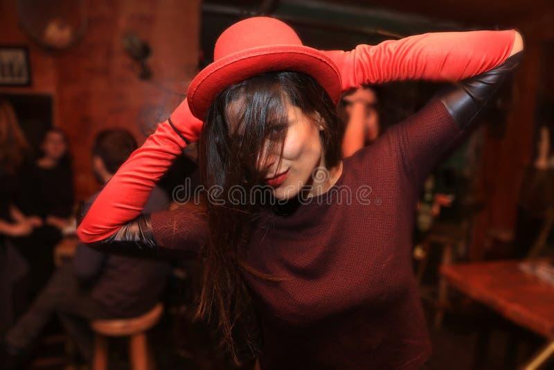 Jovem mulher alegre e bonita que sorri e que dança no clube noturno imagens de stock royalty free