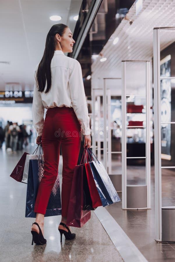 A jovem mulher alegre está comprando antes do voo imagens de stock