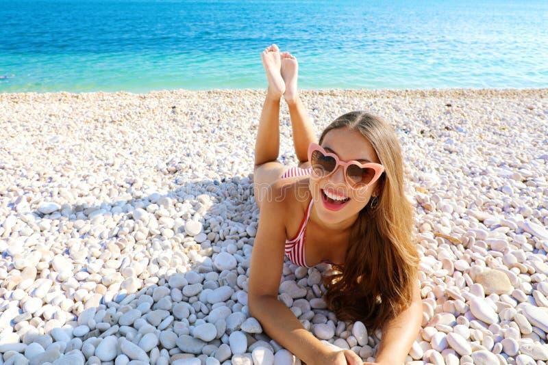 A jovem mulher alegre feliz com os óculos de sol do coração que encontram-se em seixos encalha Retrato da menina feliz em suas fé fotografia de stock