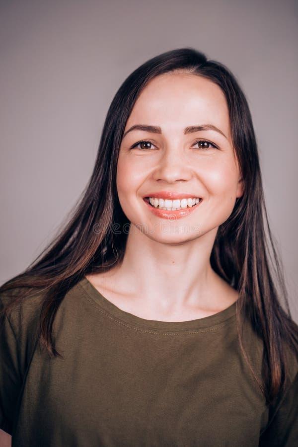 Jovem mulher alegre feliz olha a câmera e sorri foto de stock royalty free