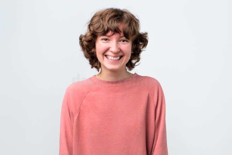 Jovem mulher alegre feliz que olha a câmera com sorriso alegre e encantador fotografia de stock royalty free