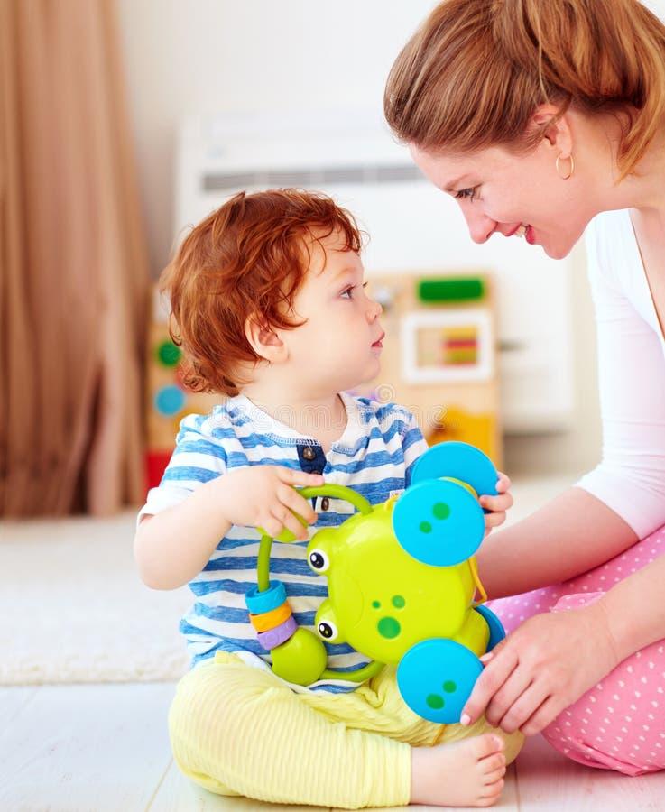 Jovem mulher alegre, mãe que joga jogos com as crianças na sala do berçário imagens de stock royalty free