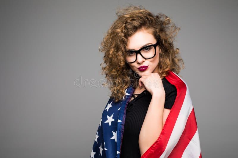 A jovem mulher alegre na roupa ocasional e nos vidros é coberta na bandeira americana e no sorriso no fundo cinzento fotos de stock