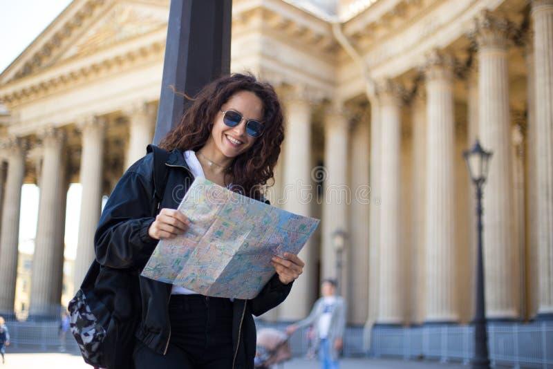 A jovem mulher alegre no preto, nos óculos de sol com um mapa do papel da cidade nas mãos, tem uma trouxa, no fundo da catedral fotografia de stock royalty free