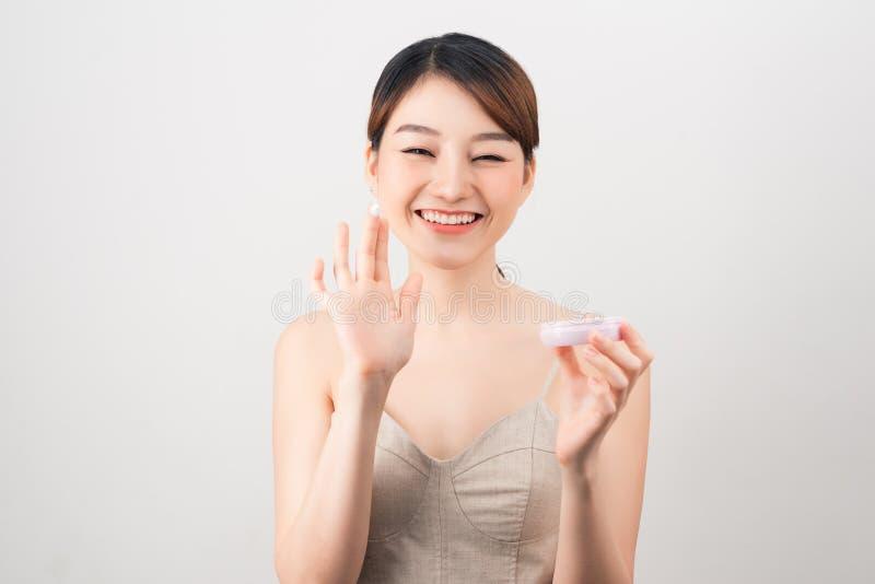 Jovem mulher alegre que aplica o creme de cara isolado no branco fotos de stock