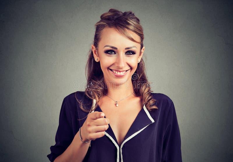 Jovem mulher alegre que aponta o dedo na câmera imagens de stock royalty free