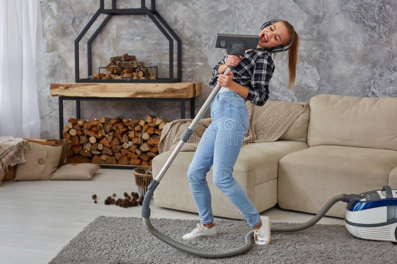 Jovem mulher alegre que aprecia o solo que canta com aspirador de p30 ao limpar a casa foto de stock royalty free