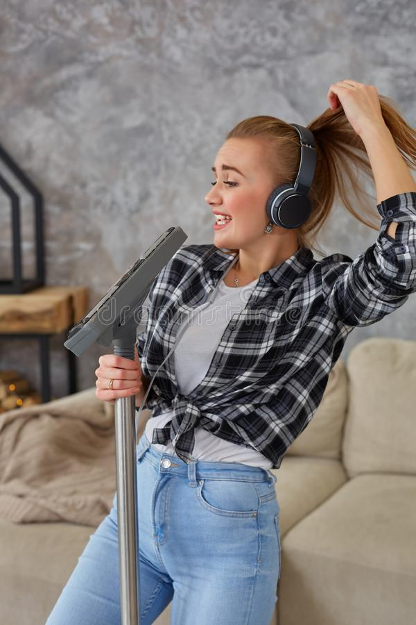 Jovem mulher alegre que aprecia o solo que canta com aspirador de p30 ao limpar a casa imagens de stock royalty free