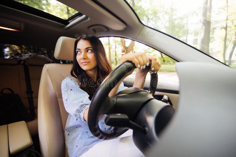 Jovem mulher alegre que aprende conduzir em seu próprio carro fotografia de stock royalty free