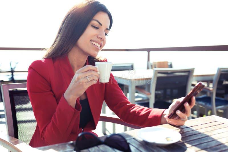 A jovem mulher alegre que bebe o quando do latte do chá verde de Matcha que texting com seu telefone celular em wodden a tabela n fotografia de stock royalty free