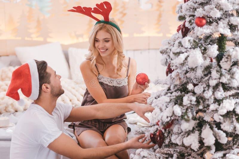 Jovem mulher alegre que decora a árvore de Natal imagem de stock