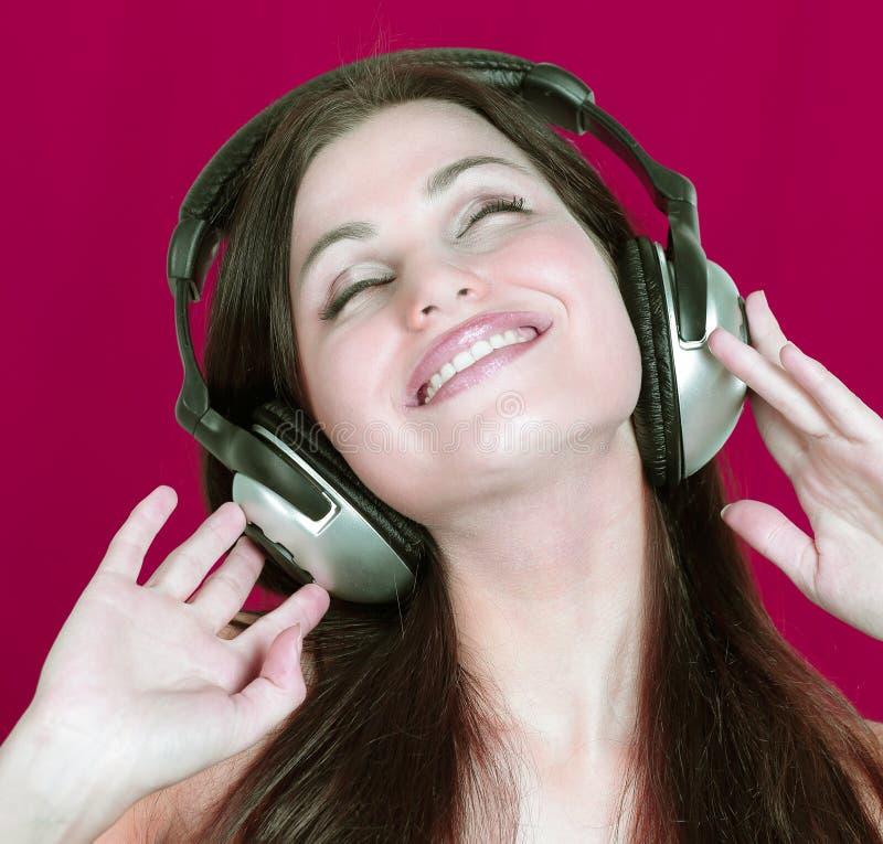 Jovem mulher alegre que escuta a música através dos fones de ouvido fotos de stock