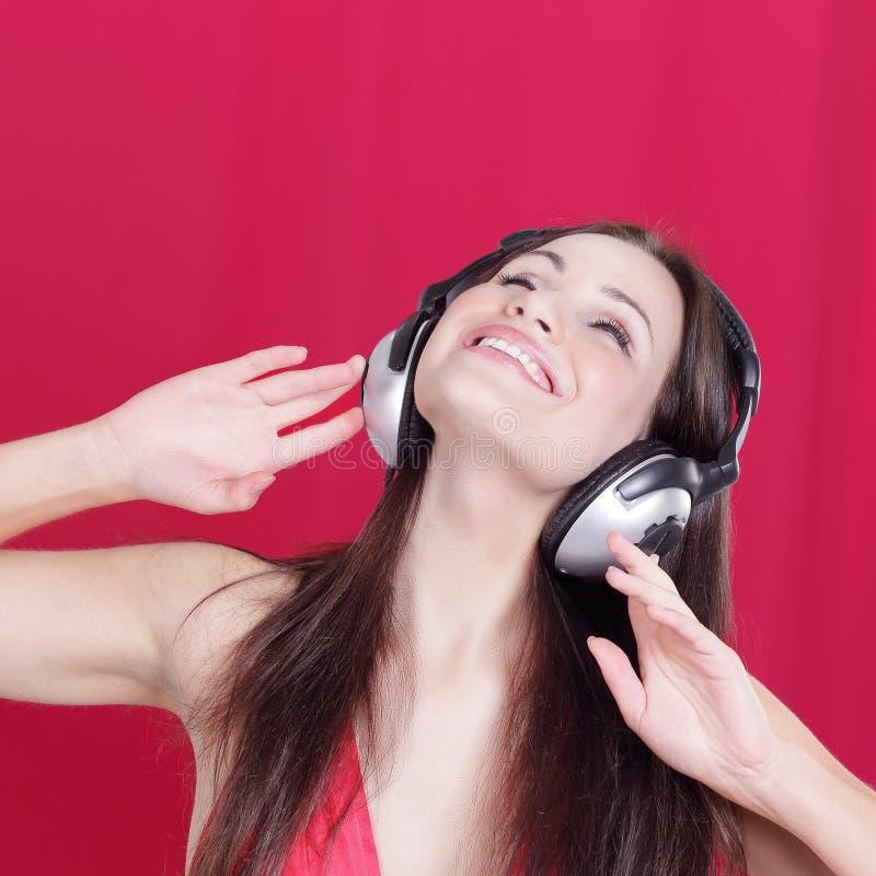 Jovem mulher alegre que escuta a música através dos fones de ouvido fotografia de stock royalty free