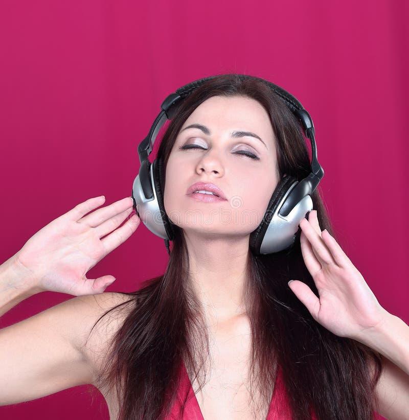 Jovem mulher alegre que escuta a m?sica atrav?s dos fones de ouvido fotografia de stock royalty free