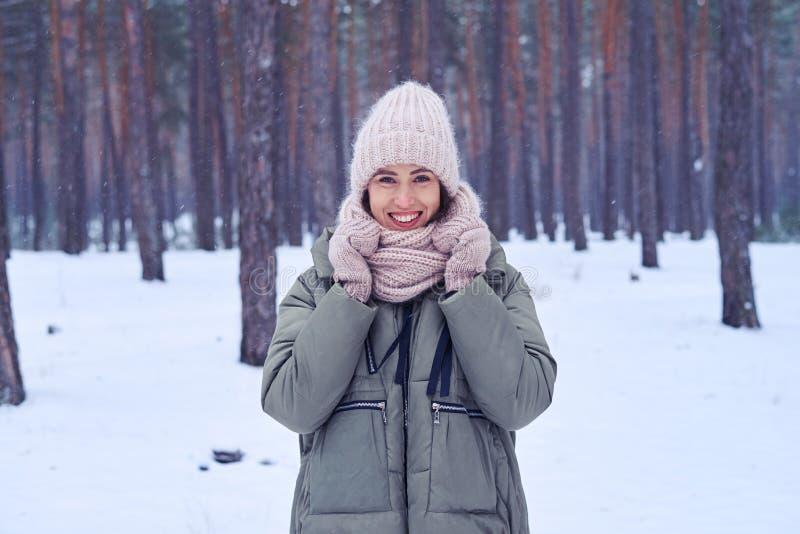 Jovem mulher alegre que está em uma floresta nevado que guarda um knitte imagem de stock