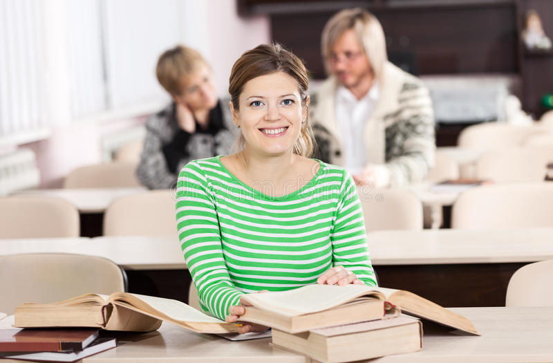 Jovem mulher alegre que estuda na mesa com lotes de imagens de stock