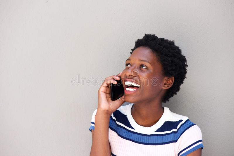 Jovem mulher alegre que fala no telefone celular contra o fundo cinzento imagens de stock royalty free