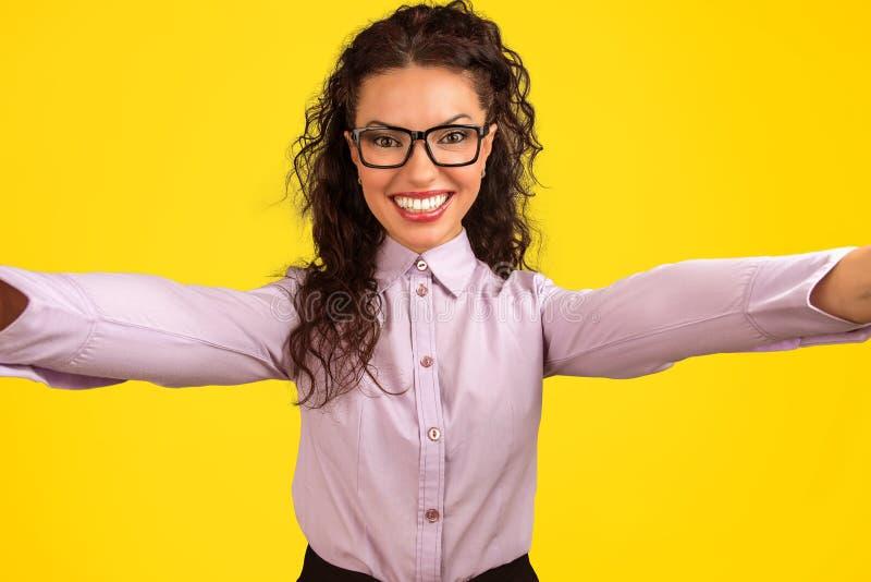 Jovem mulher alegre que olha a câmera e que toma um selfie fotos de stock