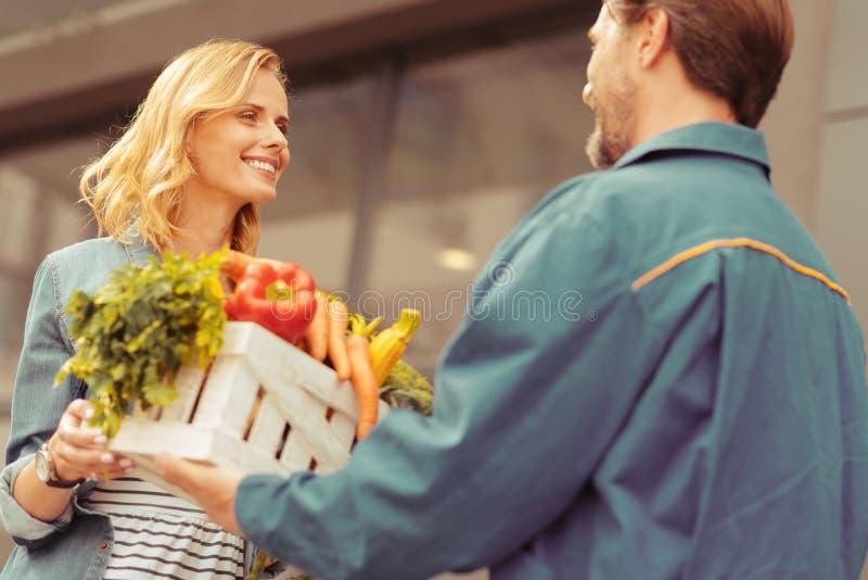 Jovem mulher alegre que toma a caixa com bens imagem de stock