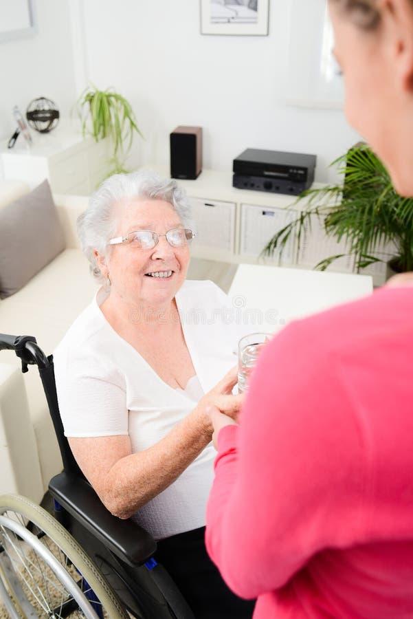 Jovem mulher alegre que toma em casa de uma mulher idosa na cadeira de rodas imagem de stock