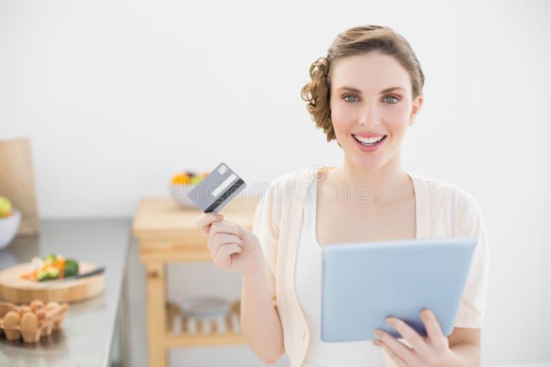 Jovem mulher alegre que usa sua tabuleta para as compras ao domicílio que sentam-se em sua cozinha imagem de stock