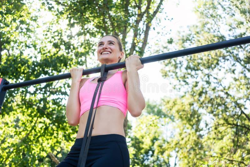 Jovem mulher alegre que veste o sutiã cor-de-rosa dos esportes ao fazer o queixo-acima imagens de stock royalty free