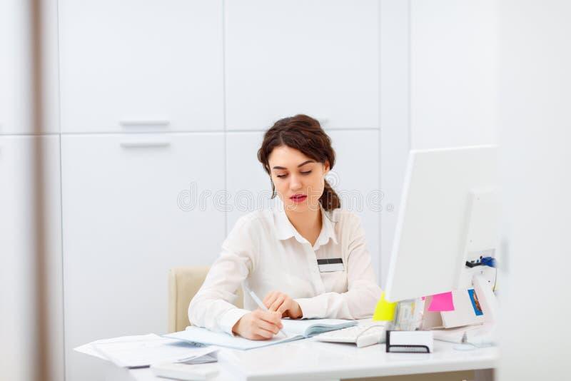 Jovem mulher amigável atrás do administrador da mesa de recepção imagem de stock