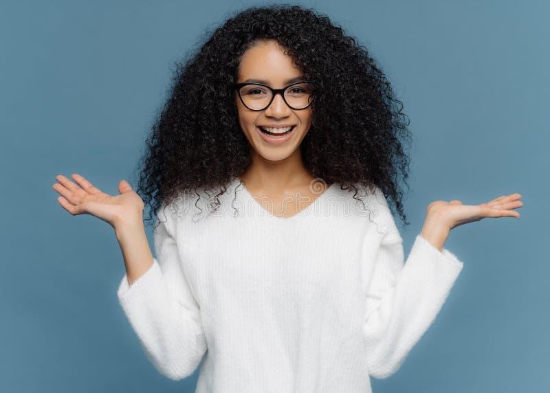 A jovem mulher amigável positiva com aparência do Afro, espalha as palmas, guarda o objeto invisível, tem o sorriso encantador, p fotos de stock royalty free