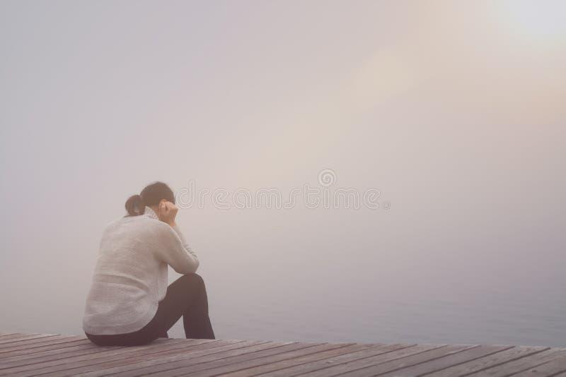 A jovem mulher anônima está sentando-se em um alargamento da lente da ponte de madeira fotos de stock royalty free
