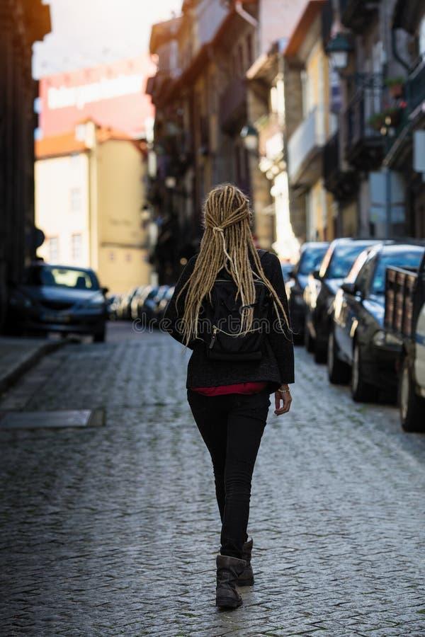 A jovem mulher anda através das ruas estreitas do pavimento imagens de stock