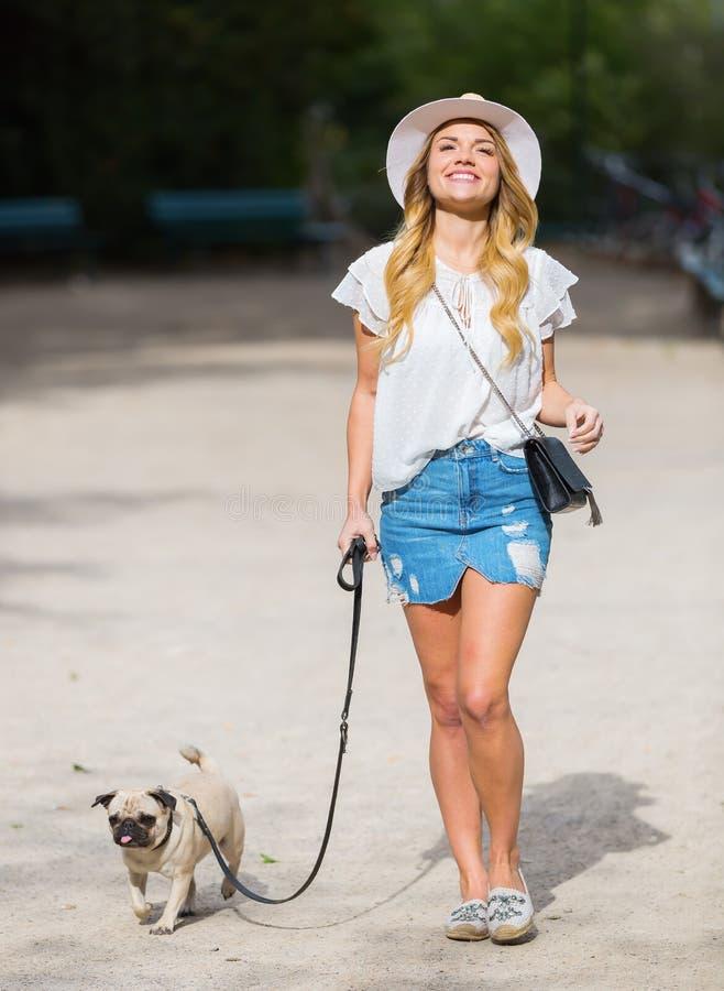 A jovem mulher anda com um pug no parque imagem de stock royalty free