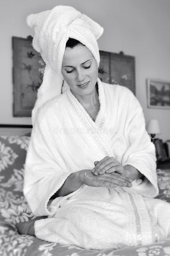A jovem mulher aplica o moisturiser a sua pele foto de stock