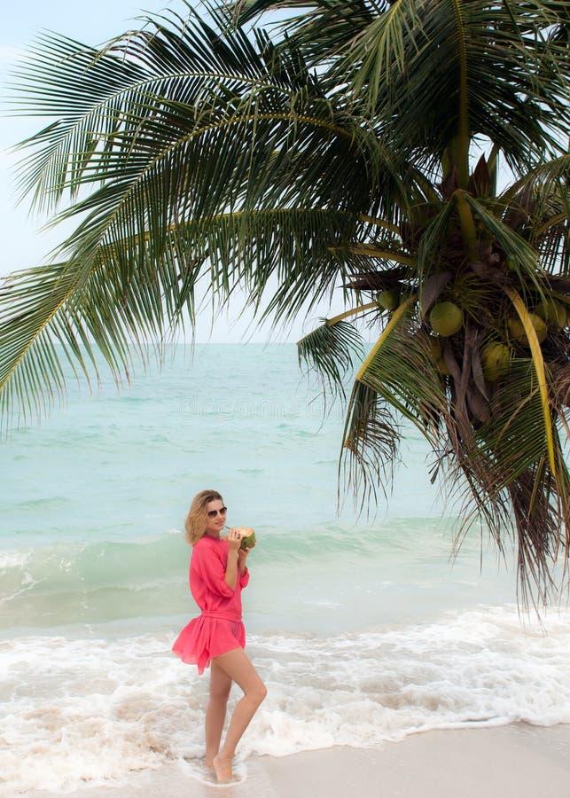 A jovem mulher aprecia o cocktail do coco na praia foto de stock royalty free