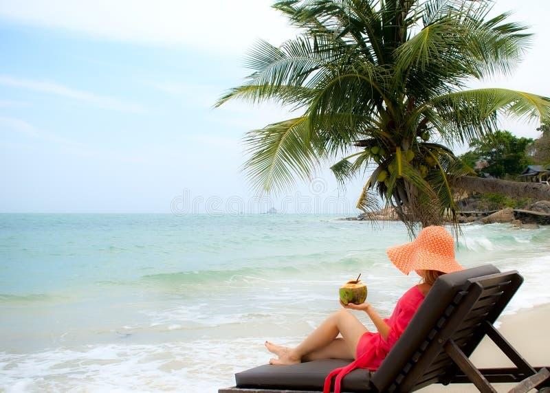 A jovem mulher aprecia o coco novo que senta-se na praia fotografia de stock royalty free