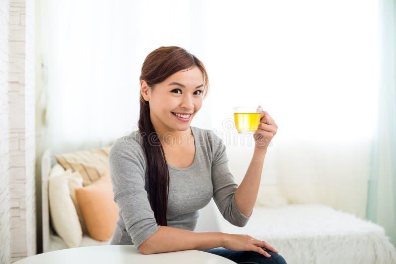 A jovem mulher aprecia seu chá imagens de stock