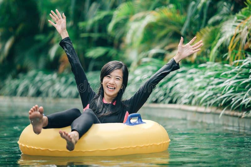 A jovem mulher aprecia a tubulação na associação preguiçosa do rio foto de stock