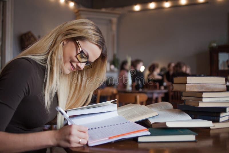 A jovem mulher aprende com prazer Preparando o exame e a aprendizagem da biblioteca das lições em público fotos de stock