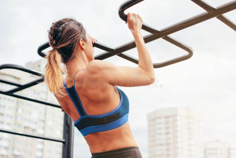 A jovem mulher apta atrativa na menina do desgaste do esporte levanta na barra na área do exercício da rua O estilo de vida saud? fotos de stock