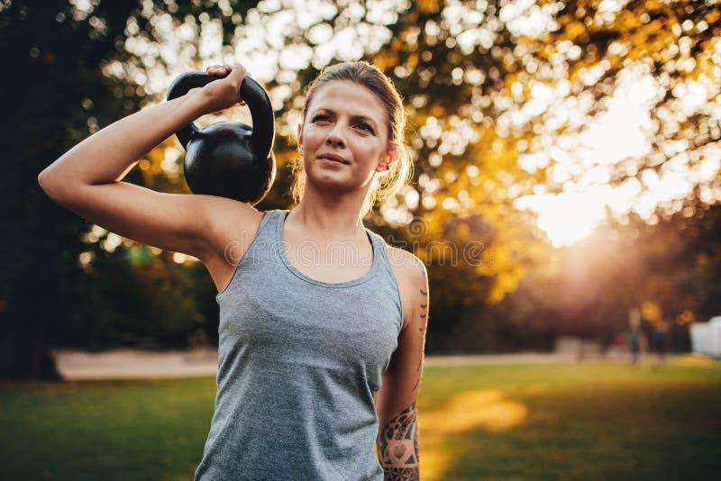 Jovem mulher apta com pesos do kettlebell no parque imagem de stock royalty free