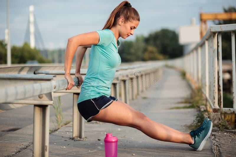 Jovem mulher apta determinada que exercita em uma ponte fotografia de stock royalty free