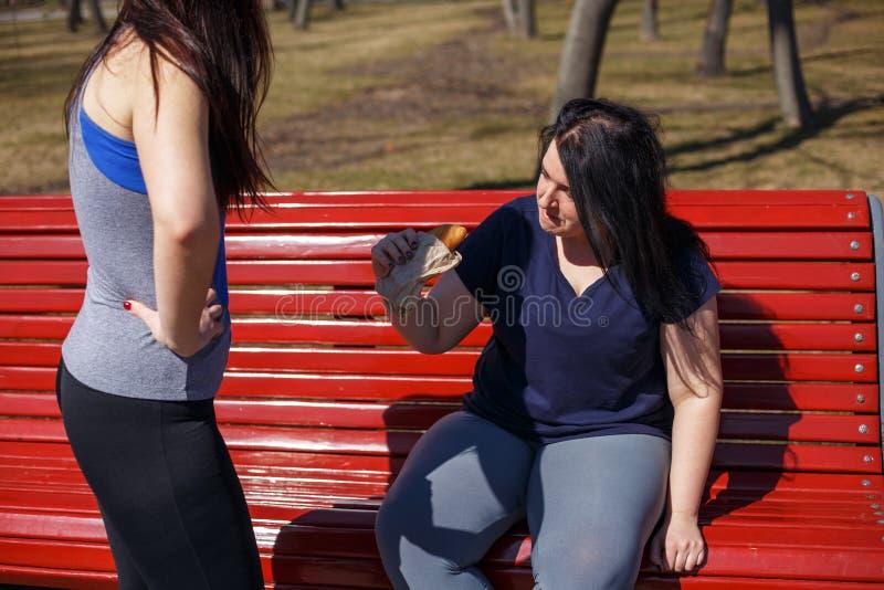 A jovem mulher apta motiva seu amigo para parar de comer a comida lixo Ele imagem de stock