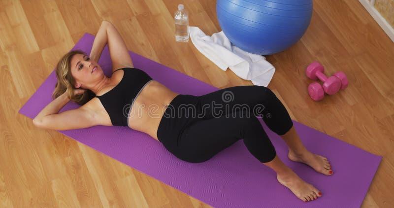 Jovem mulher apta que exercita no gym home imagem de stock