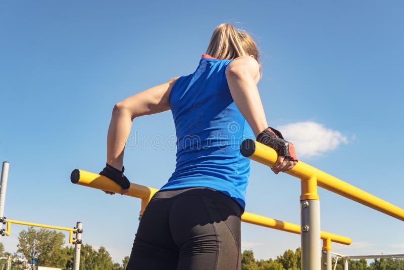 Jovem mulher apta que guarda o equilíbrio nas barras paralelas Trens louros da menina fora no parque Treinamento do bíceps e imagens de stock